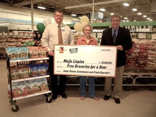 Maija Liepins (center) was awarded a giant-sized check that represents free groceries for a year at her favorite store, Meijer. Presenting the check are Ed Cunningham, Supermarket Manager, Meijer (left) and Jim McMath, Regional Sales Manager, Fresh Gourmet Company (right).